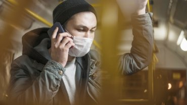 side-view-man-talking-phone-bus-while-wearing-covid-19-mask