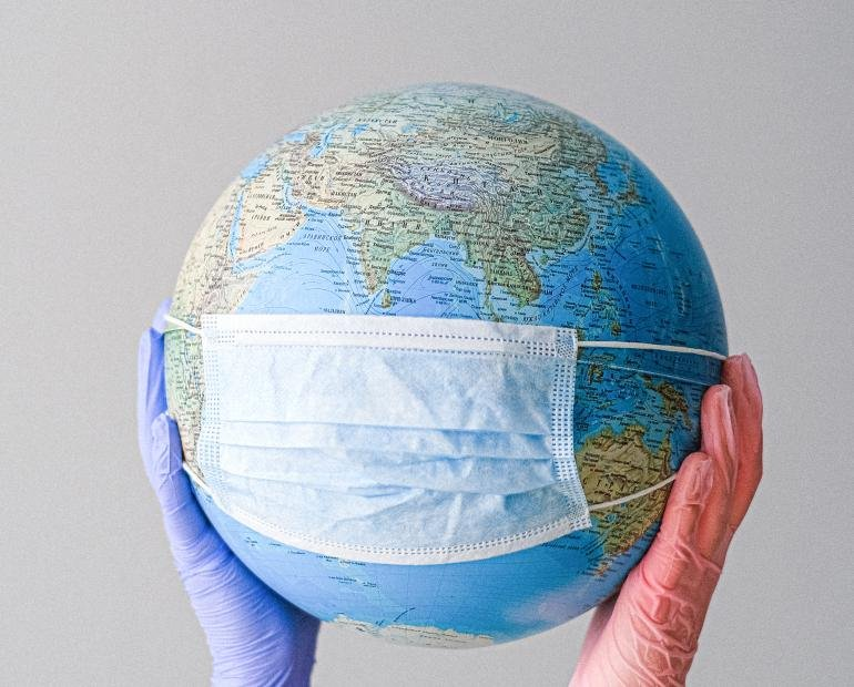 canva_hands_with_latex_gloves_holding_a_globe_with_a_face_mask