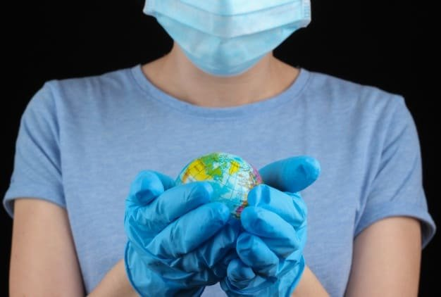 woman-medical-protective-mask-holding-earth