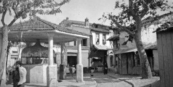 Η πλατεία το 1935 με τον φακό της Έλλης Παπαδημητρίου. Εκτός από την βρύση και τα δέντρα που κοσμούν την πλατεία, ο σχηματισμένος δρόμος με τους μπαβέδες που ξεκινούσε από την Πόρτα Μαγγιόρε, περνούσε από την πλατεία και οδηγούσε στον οικισμό, 1935, Αρχεί